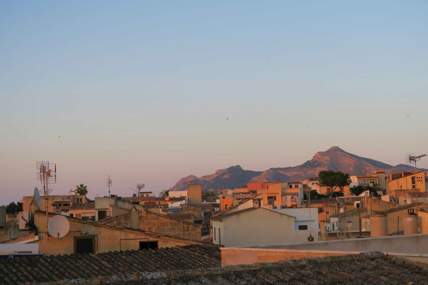 sunset on roof tops with mountain in the background in Alcudia old town in Mallorca, Spain