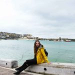 girl sitting on st ives harbour