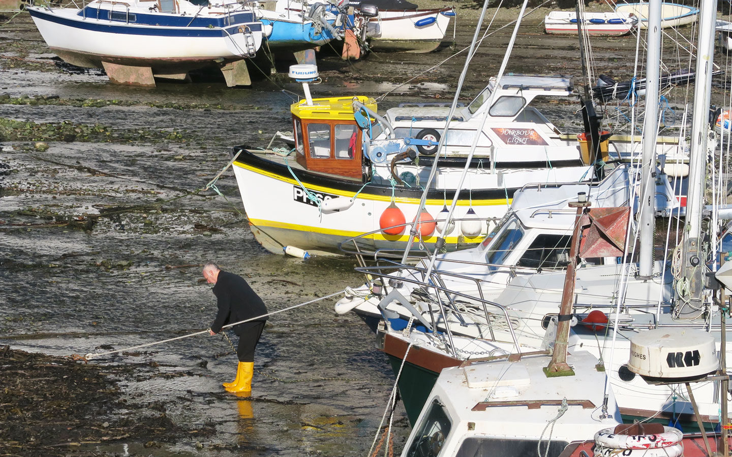 fisherman in yellow wellies in polperro harbour