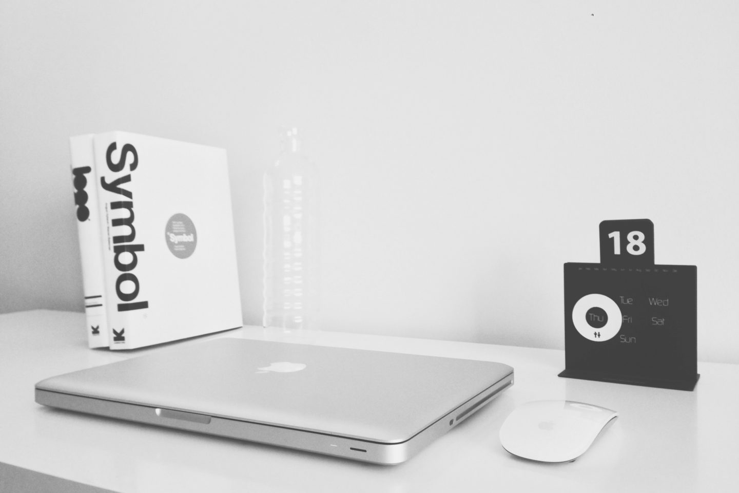 black and white photo of mac book on a graphic designers desk