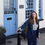 melissa carne wearing navy jacket in front of a cottage in looe in cornwall