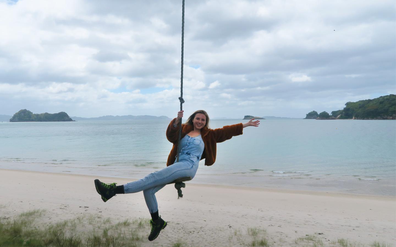 melissa carne on rope swing on hahei beach in new zealand