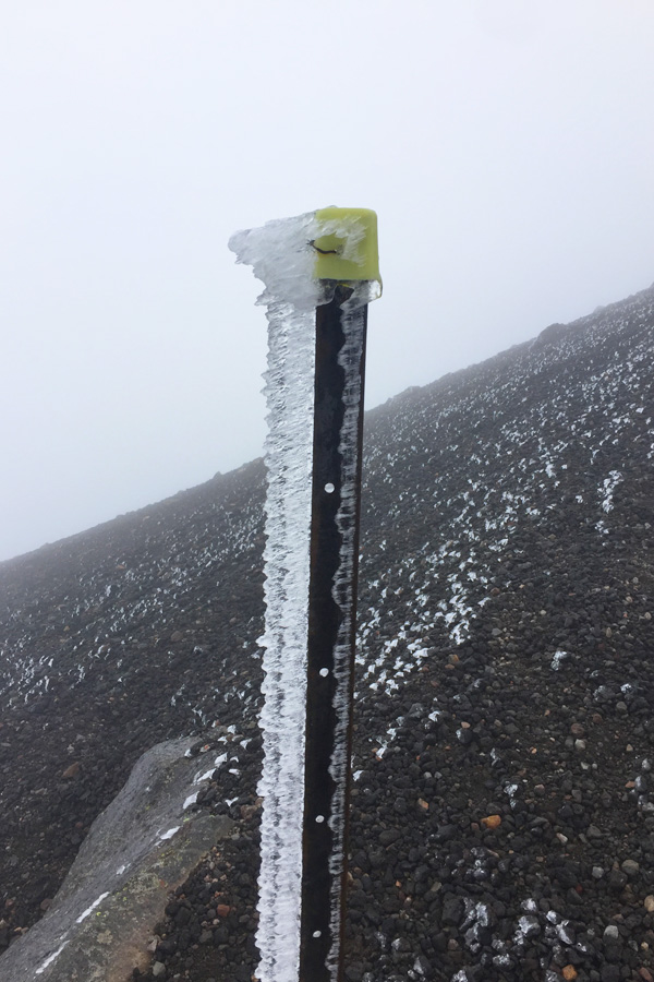 frozen ice on a pole on tongariro alpine crossing in new zealand