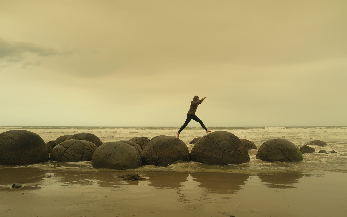 girl jumping on moeraki boulders in new zealand